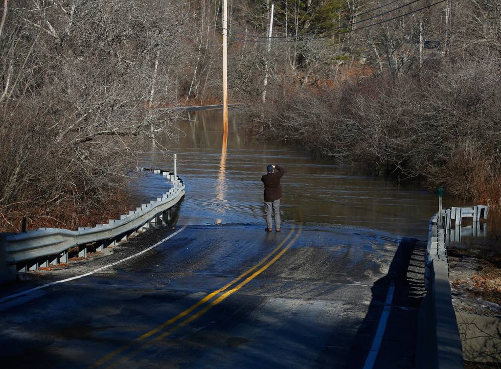 North Yarmouth resident Mike Estes takes pictures of a submerged section of West Pownal Road on Monday following a rainstorm that knocked out power to over 50,000 Maine homes.
