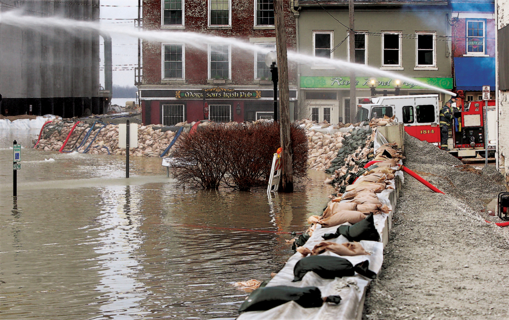Firemen spray water towards water seepage under the city's makeshift flood levee in downtown Alton, Ill., Wednesday.