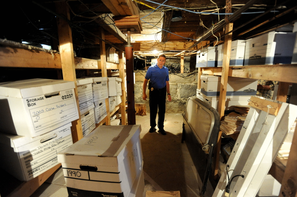 Michael Tracy, chief of the Oakland Police Department, stands in July in the police station basement where documents are stored. The station, in a cramped farmhouse, will be replaced soon by a new building. The town might consider bids on the work next week.