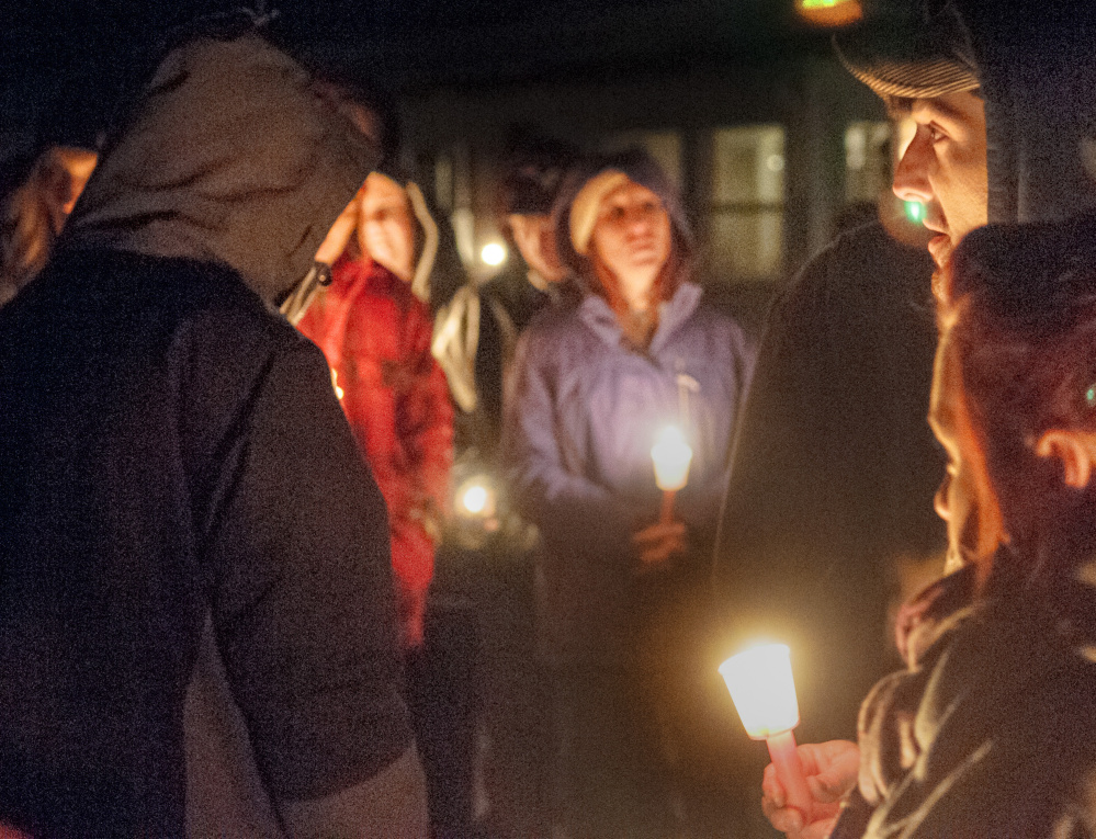 David Jordan, top right, leads The Lord's Prayer during a candlelight vigil Friday in Augusta in remembrance of Eric Williams, 35 and Bonnie Royer, 26, who were shot to death early Christmas morning in Manchester.