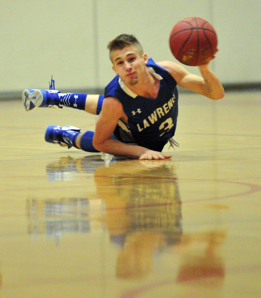 Lawrence's Walker Thomas looks to pass after scrambling on the floor for a loose ball during a game against Cony on Saturday at Cony High in Augusta.