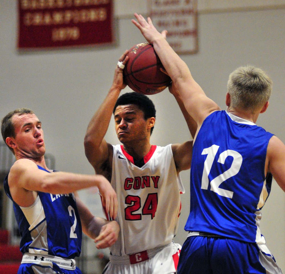 Cony's Jordan Roddy (24) goes for shot while being defended by Lawrence's J.T. Nutting, left, and Brandon Hill (12) during a game Saturday at Cony High in Augusta.