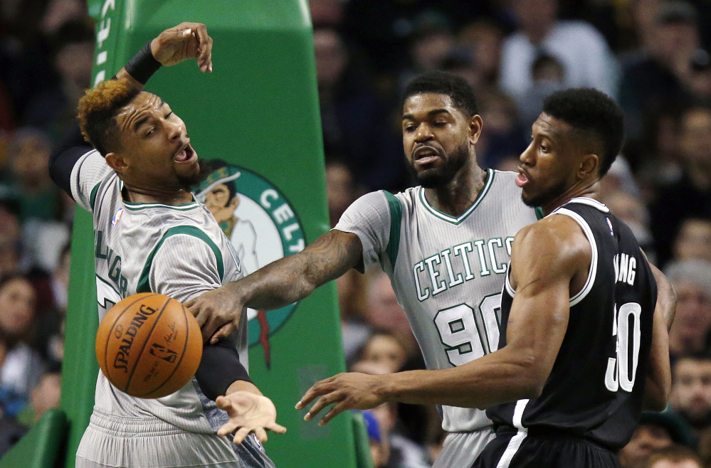 Boston's Jared Sullinger, left, and Amir Johnson (90) and Brooklyn's Thaddeus Young battle for the ball Saturday in Boston.