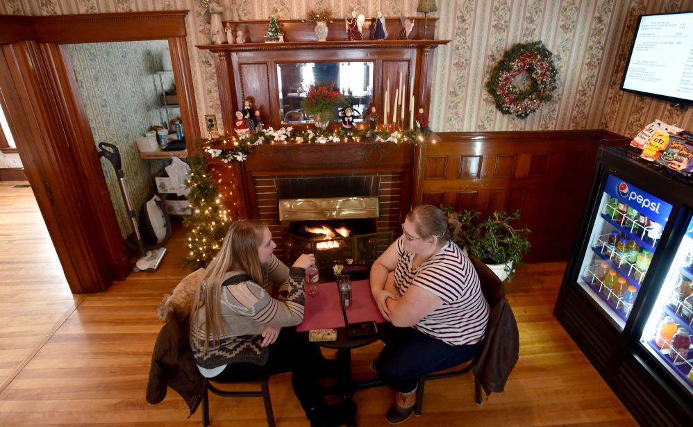 Erika Parker, left, and Anna Lorette, right, sip on coffee as they warm by the fire at M&M's Ice Cream Parlor and Fireside cafe on Main Street in Madison on Thursday.