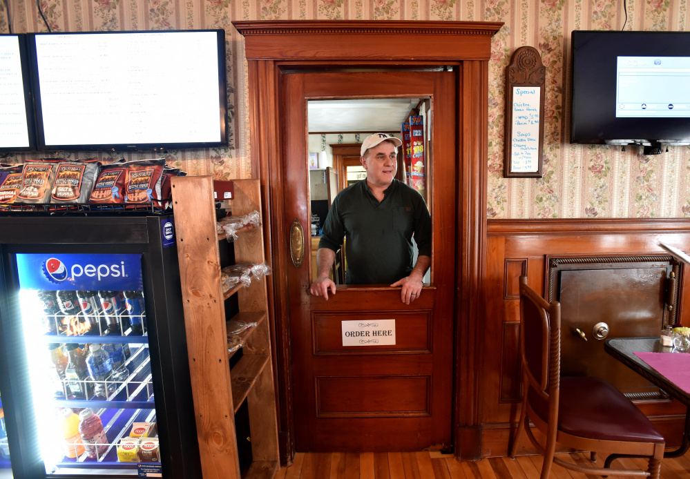 Mike Pelletier, owner of M&M's Ice Cream Parlor and Fireside Cafe on Main Street in Madison waits to take an order on Thursday. He and his wife, Mary Jane, opened the business in November and are looking forward to a great 2016, he said.