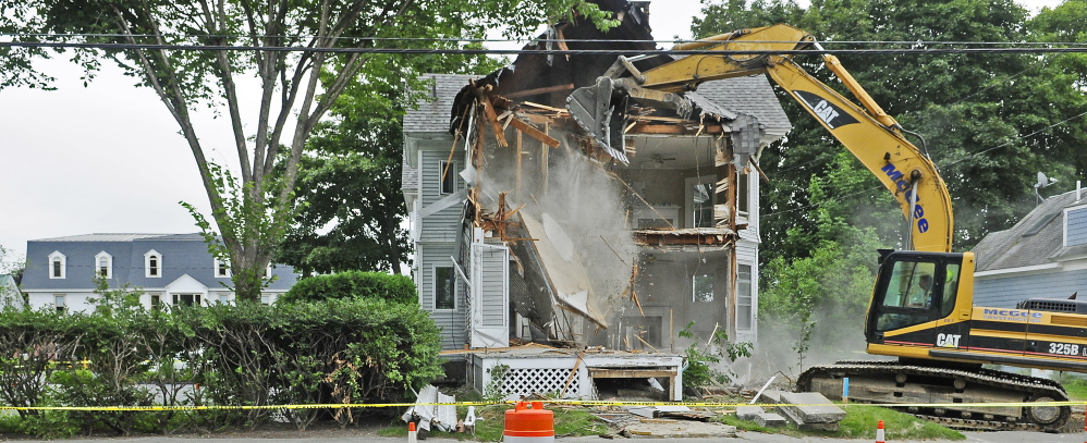 A McGee Construction excavator operator tears down 53 Chapel St. on Aug. 20 in Augusta as part of Kennebec Saving Bank's expansion of its parking area and entrance.