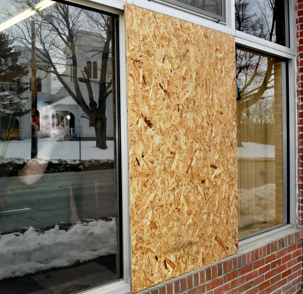 Standing beside a boarded-up window inside Dysart's Travel Stop store in Pittsfield on Sunday, employee Nicole Smith points to one of four holes made by vandals with a pellet gun since late last week.