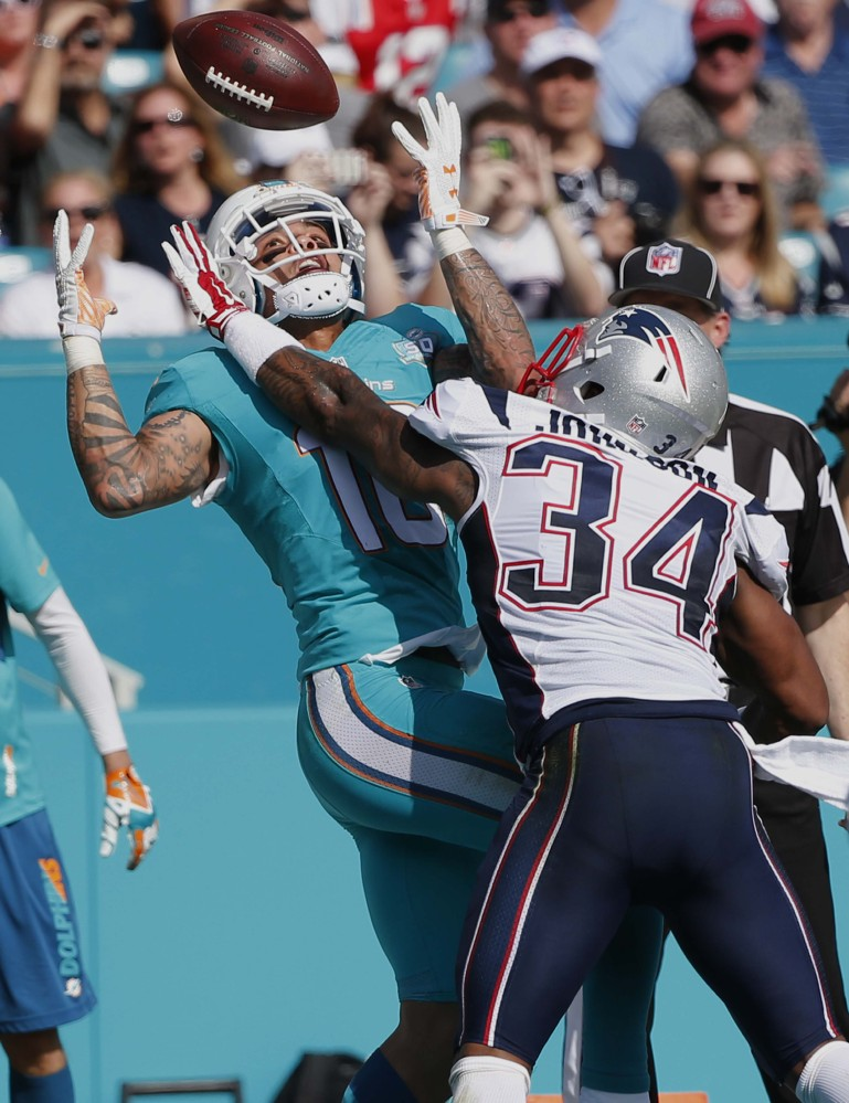 Miami Dolphins wide receiver Kenny Stills (10) is unable to hold onto a pass as New England Patriots cornerback Leonard Johnson (34) defends during the first half Sunday in Miami Gardens, Florida.