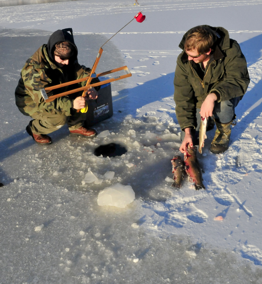 Ice fishermen braved the thin ice on McGrath Pond in Oakland to fish on Monday. Tyler Lunt, left, rebaits a fishing trap as Zack Vashon lines up the catch of brook trout.