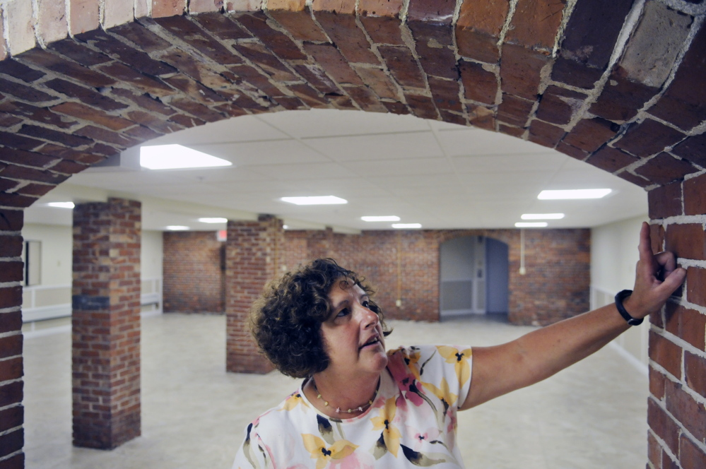 Gardiner Public Library Director Anne Davis inspects brick work in the recently renovated archivist room in the library's basement in this September file photo.