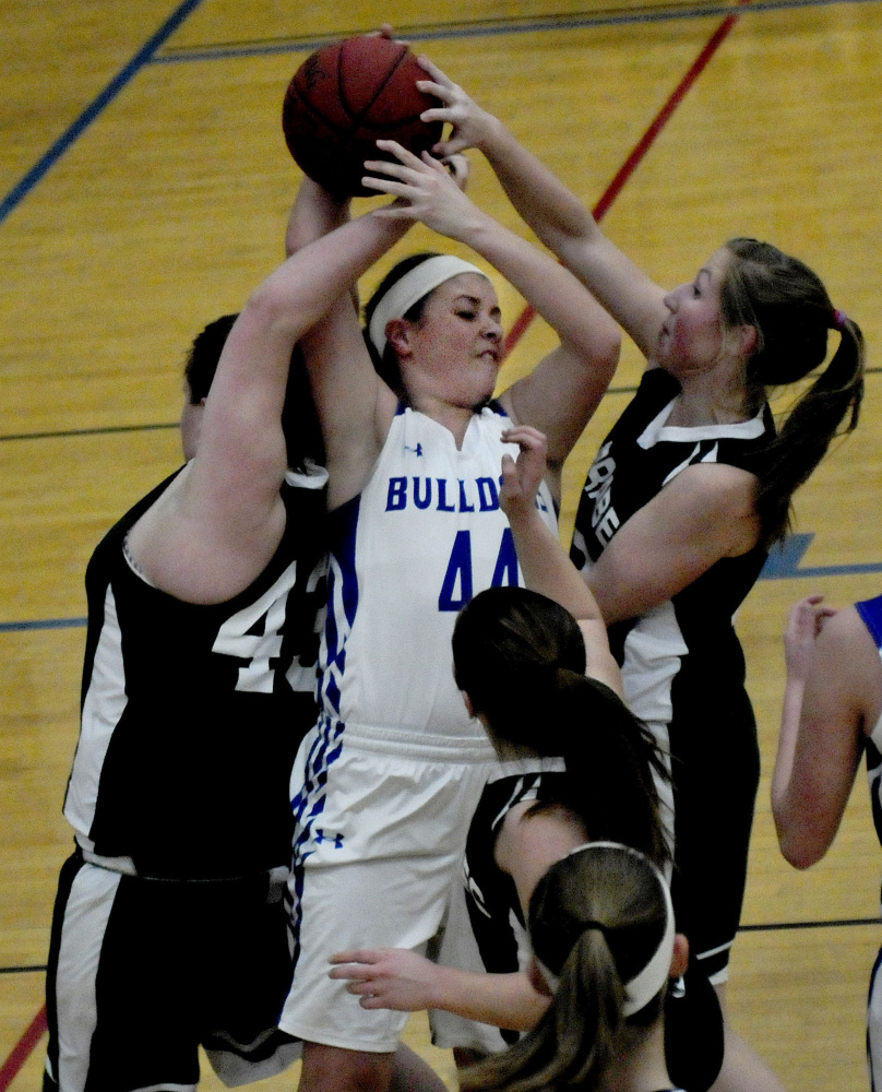 Madison's Erin Whalen is boxed in by a swarming Carrabec defense during a Mountain Valley Conference game Monday night in Madison.