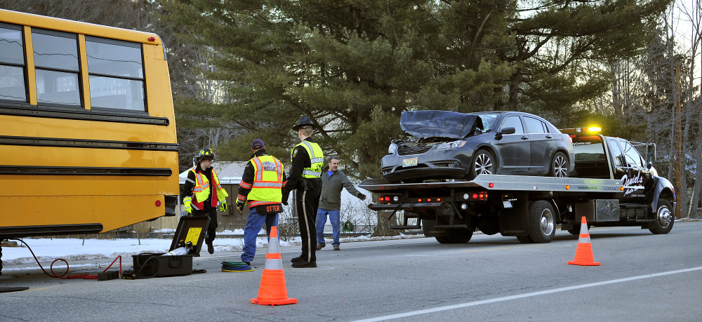 Gardiner firefighters and police officers, along with a tow truck driver, work at the scene of a collision between a car and a school bus on Tuesday on U.S. Route 201 in Gardiner.