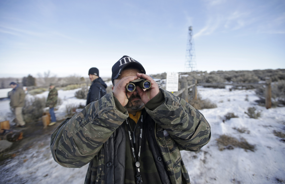 Sean Anderson, of Idaho, a supporter of the group occupying the Malheur National Wildlife Refuge, looks through binoculars at the front gate Wednesday near Burns, Ore.