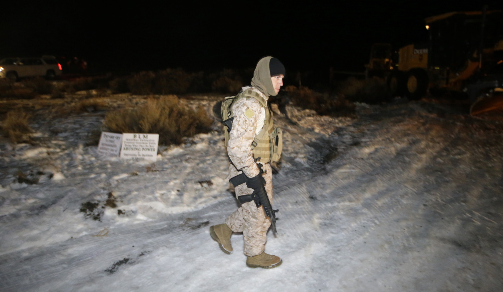 A member of the group occupying the Malheur National Wildlife Refuge headquarters stands guard Tuesday near Burns, Ore.