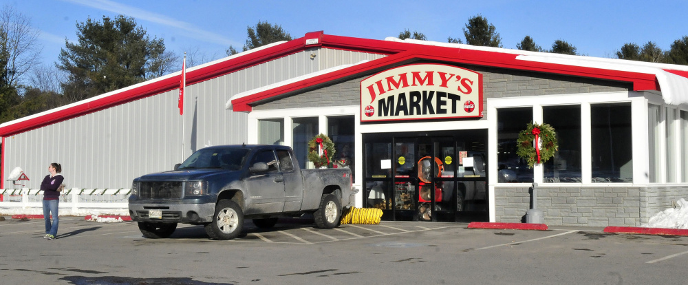 An employee stands outside Jimmy's Market in Bingham as large fans ventilate the building that was closed Wednesday because of a fire ignited by a spark from a cutting torch.