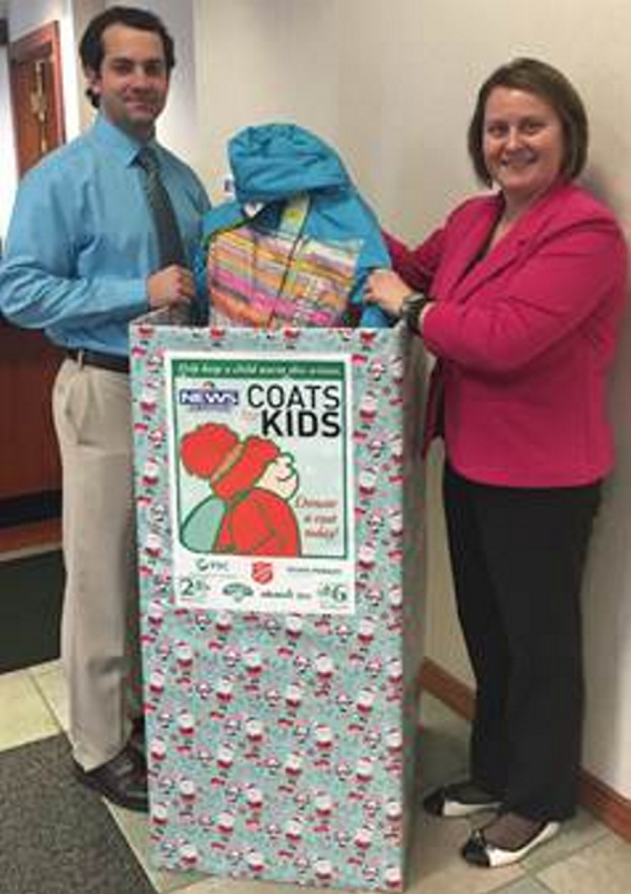 Anthony Sementelli, a seasonal teller, and Susan Albert, a teller in Waterville, with a coat that was dropped off at the Waterville branch.