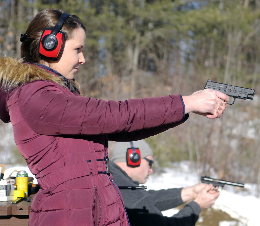 """Katherine Pollock fires a pistol with Rob Sibley on Wednesday at an Inland Fisheries and Wildlife range in Augusta. Sibley said he doesn't agree with President Obama's executive actions to order more background checks on guns purchases. """"But I think his heart is in the right place,"""" the Augusta resident said. A Richmond native who lives in Connecticut, Pollock said she wants to learn how to shoot."""
