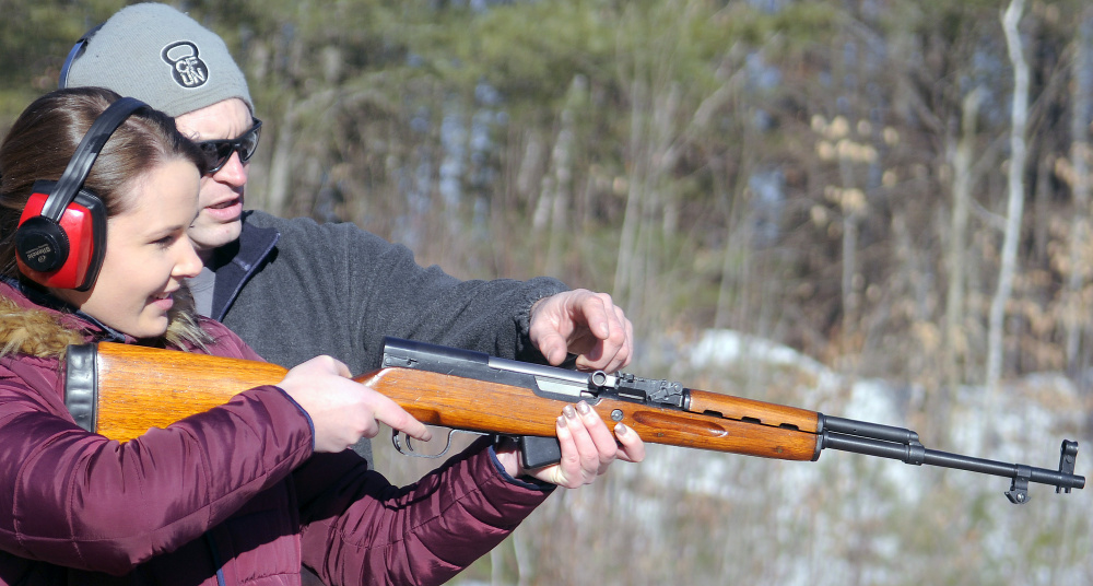 Katherine Pollock fires a rifle under the instruction of Rob Sibley on Wednesday at an Inland Fisheries and Wildlife range in Augusta.