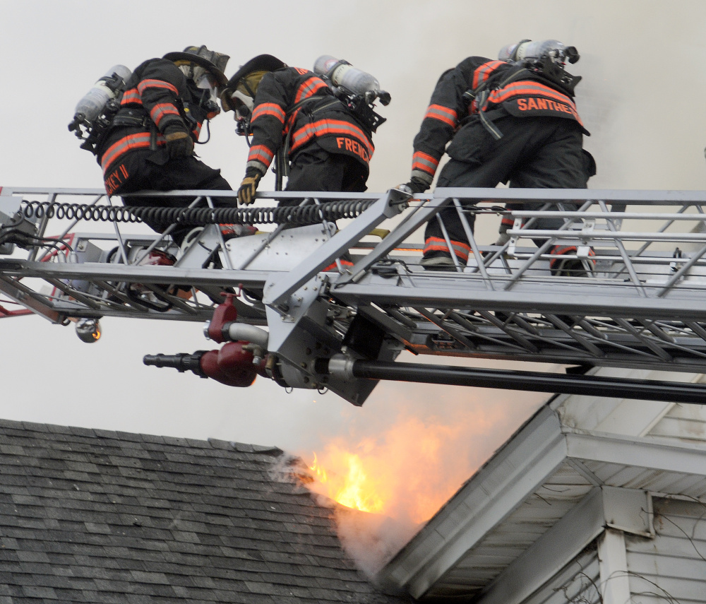 Gardiner firefighters pull a colleague to safety Wednesday after he broke through the roof 37 Riverview Drive in Gardiner.