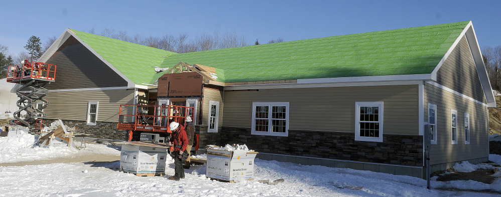Kavestone LLC builders work Wednesday on the exterior of the new Belgrade Town Office, which is scheduled to open in the spring.
