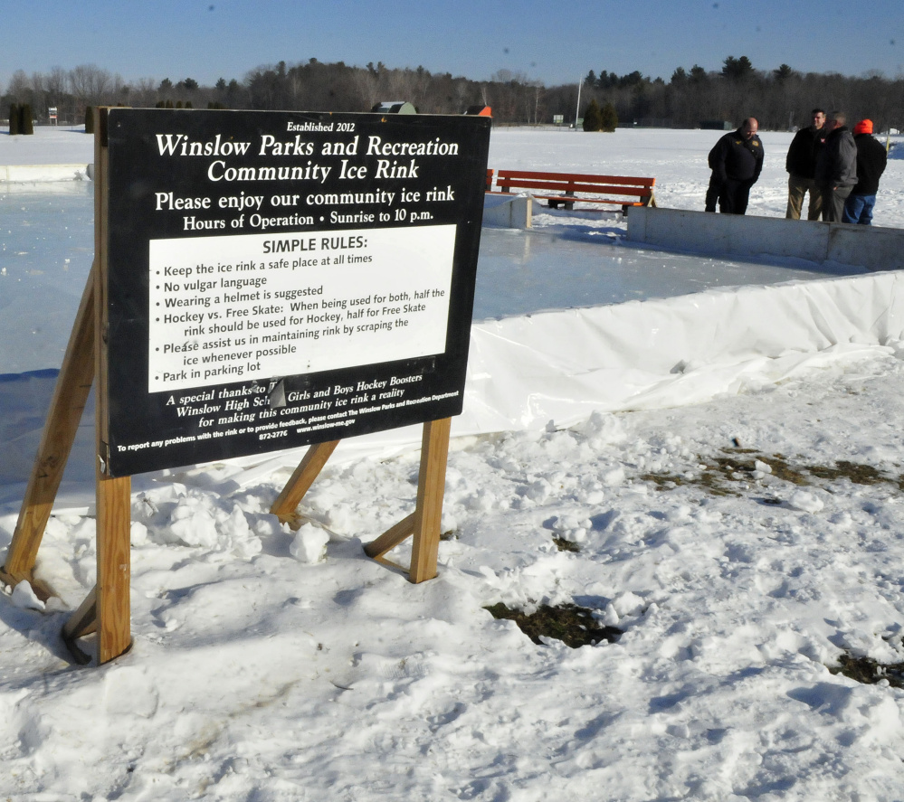 Contributors talk about creating an outdoor ice skating rink in Winslow Thursday. The rink opens Saturday.