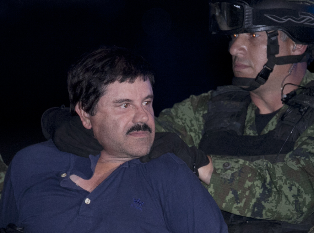 "Joaquin ""El Chapo"" Guzman is made to face the press as he is escorted to a helicopter in handcuffs by Mexican soldiers and marines at a federal hangar in Mexico City, Mexico, Friday."