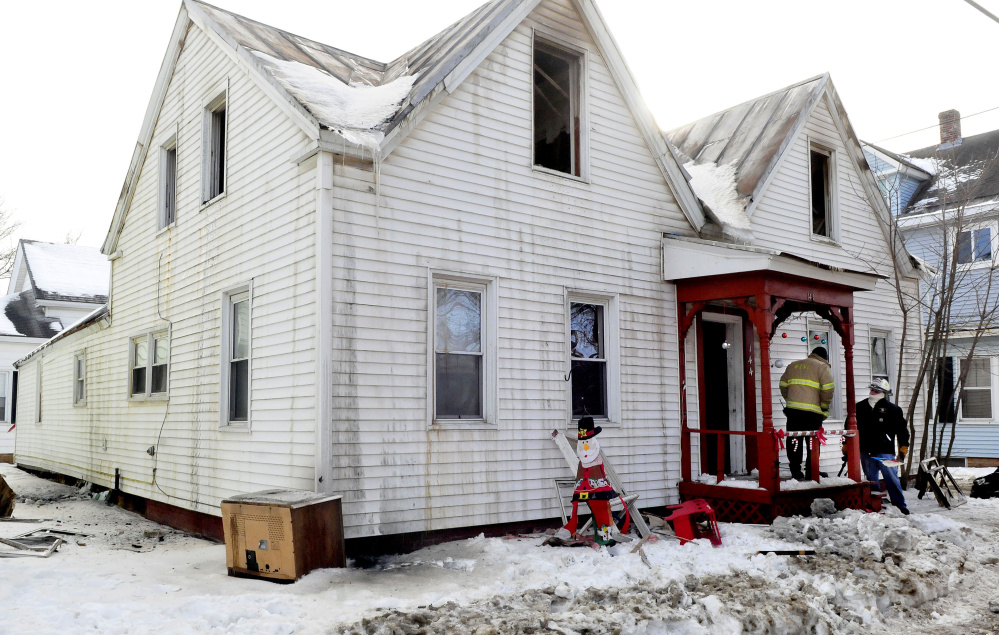 Waterville firefighter Ryan Johnston, left, confers with Ken MacMaster, an investigator with the Office of the State Fire Marshal, at 144 Water St. in Waterville, a house that was destroyed by fire Jan. 3-4. The family that was renting the home plans to move back to South Carolina.