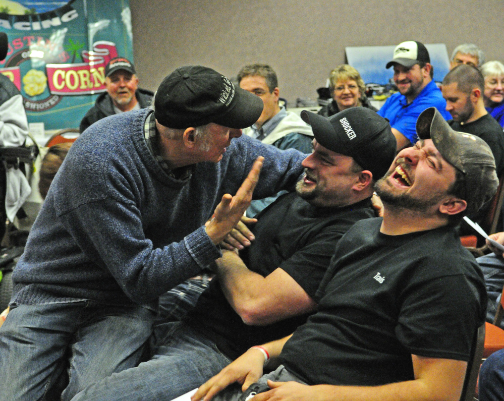 Rosey Gerry, left, sits in Zach Audet's lap while cajoling him to bid higher during an auction Saturday at the Augusta Civic Center. Travis Pouliot laughs during the fundraiser for the Maine Vintage Race Car Association.