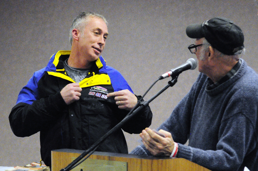 Retired professional stock car racer Andy Santerre, left, models a jacket autographed by him and two other professional drivers that Rosey Gerry is about to auction off Saturday at the Augusta Civic Center. The event was a fundraiser for the Maine Vintage Race Car Association.