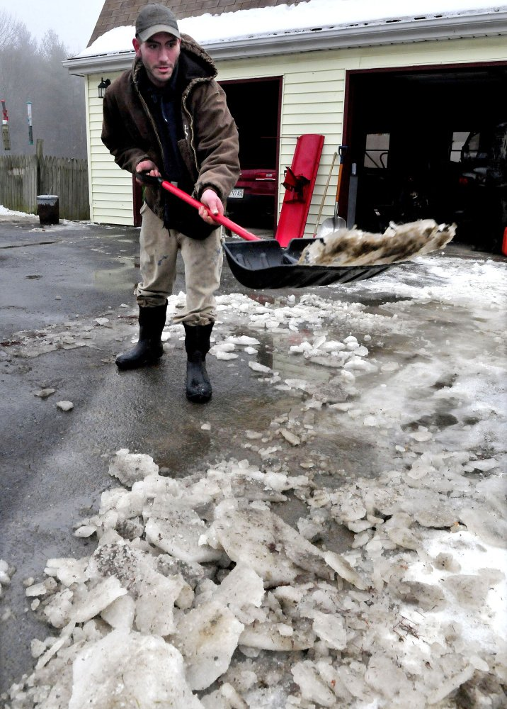 OAKLAND,  ME-  January 10: James Gray throws slush and chunks of ice  that melted on the driveway at his home in Oakland on a warm and rainy Sunday, January 10, 2016.  (Photo by David Leaming/Staff Photographer)