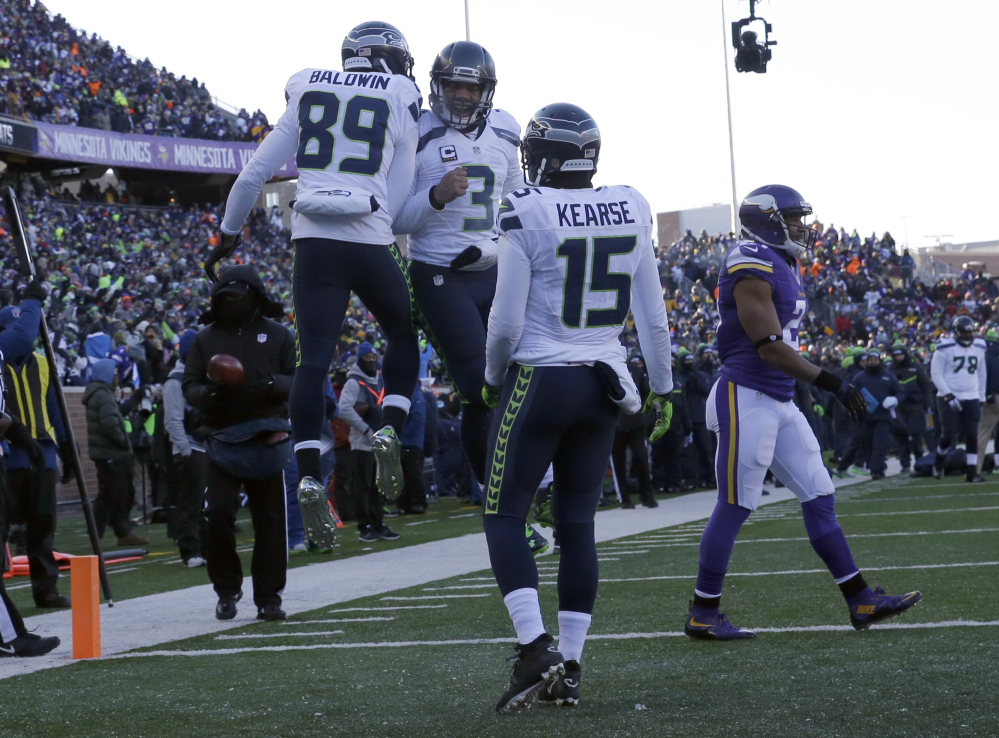 Seahawks wide receiver Doug Baldwin, 89, and quarterback Russell Wilson celebrate a touchdown as wide receiver Jermaine Kearse joins during the second half of Sunday's game playoff at Minneapolis. The Seahawks won, 10-9.