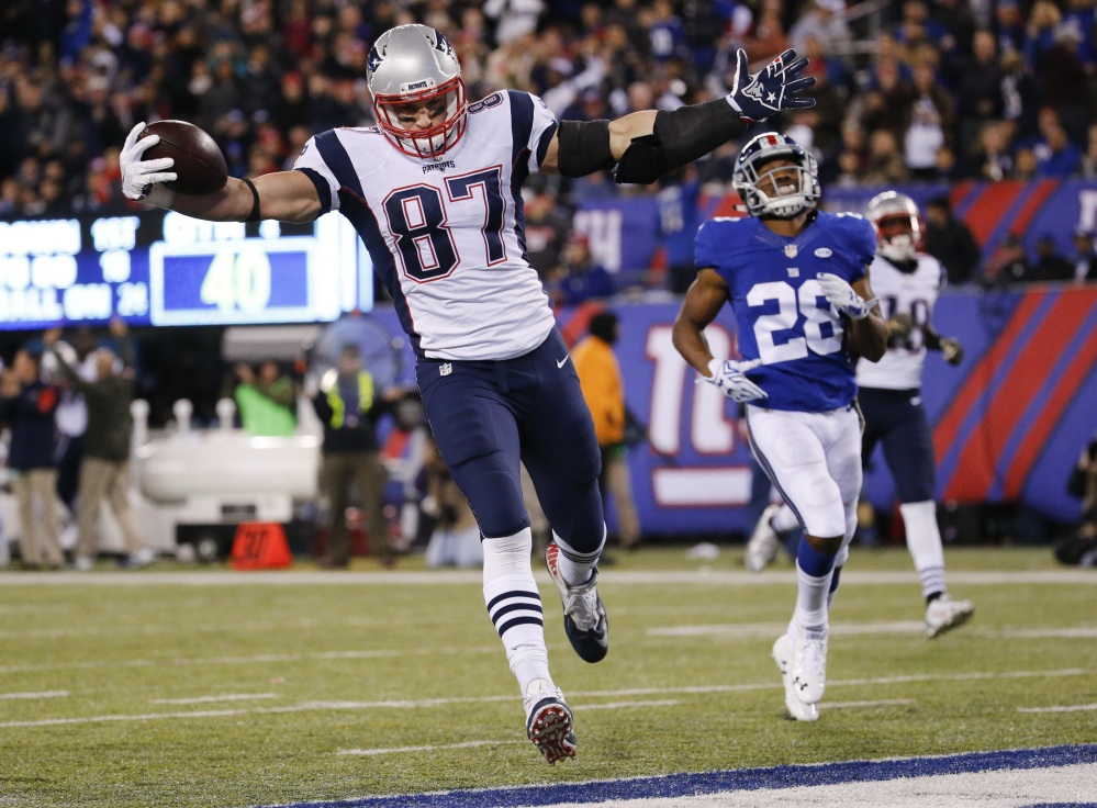 New England's Rob Gronkowski scores a touchdown in front of New York Giants' Jayron Hosley (28) during the second half earlier this season in East Rutherford, N.J. Gronkowski and the Patriots will host the Kansas City Chiefs in an AFC divisional round playoff game Saturday.
