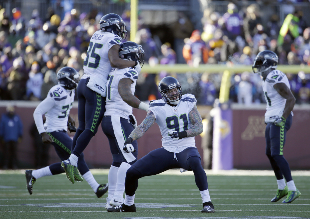 Seattle Seahawks defensive end Cassius Marsh (91) and defensive players celebrate a play against the Minnesota Vikings during an NFL wild-card game Sunday in Minneapolis.
