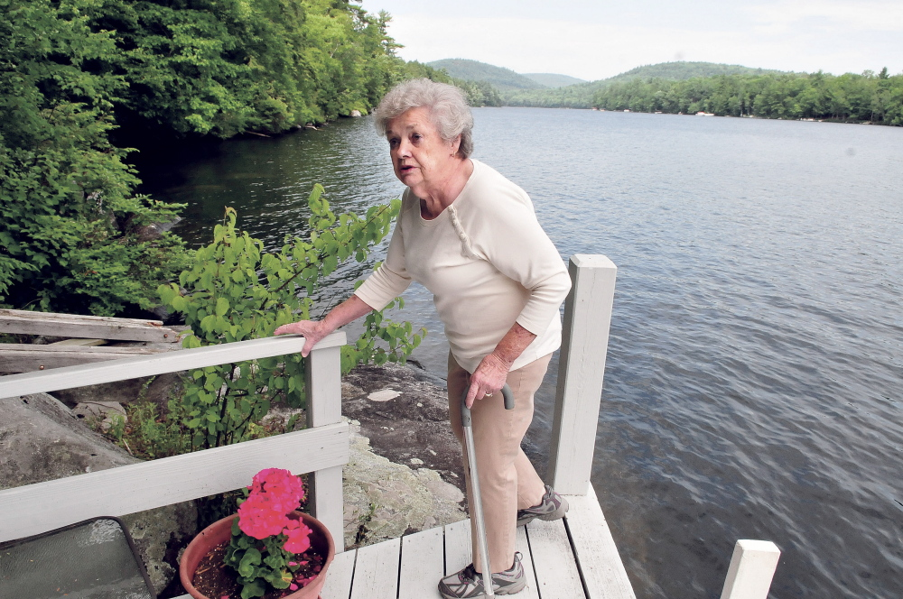 Doris Jorgensen speaks on July 14 about her concerns of a proposed children's summer camp being built along the shore behind her on Long Pond beside her property in Rome.