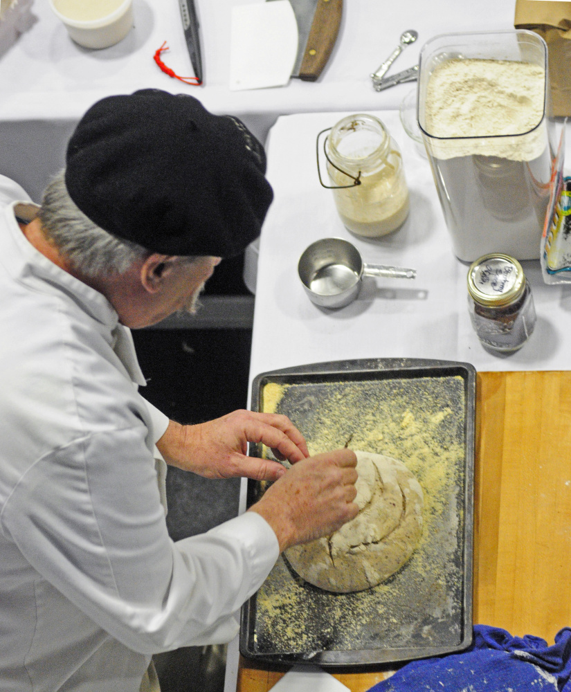 Jim Amaral, of Borealis Breads, slits the top of a loaf with a razor blade during an artisanal bread baking demonstration on Wednesday as part of the Maine Agricultural Trades Show in the Augusta Civic Center.
