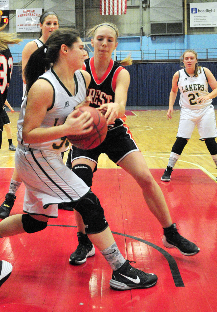Rangeley's Sydney Royce, left, and Forest Hills' Caitlin Logston battle for rebound during a Dec. 31 game in the Augusta Civic Center. Royce, a sophomore, starts for the fast-charing Lakers.