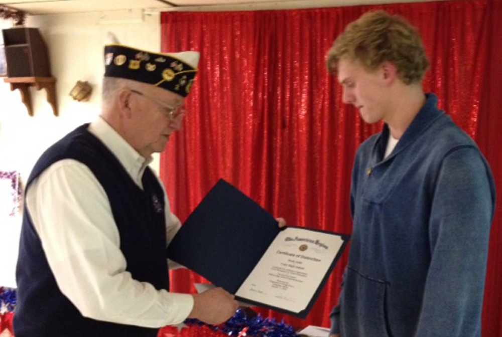Fitzgerald-Cummings Post 2 Commander Pat Eisenhart presents a scholarship and certificate of distinction to Cony High School senior Noah Aube.