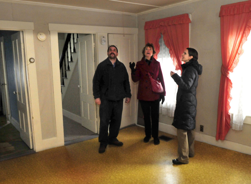 Members of the Waterville Community Land Trust, including Scott McAdoo, Vice President Nancy Williams, center, and President Ashley Pullen, on Tuesday look over the inside of the first home that will be made available through the trust as affordable housing at 181 Water St. in Waterville on Tuesday.