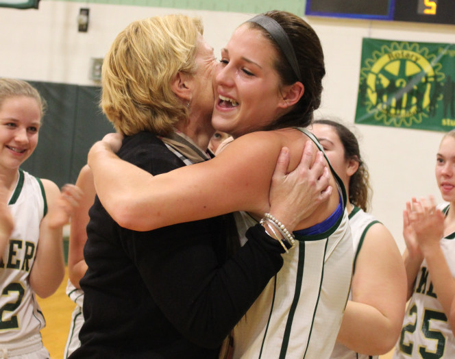 Rangeley senior Blayke Morin, right, receives a congratulatory hug from coach Heidi Deery after Morin scored her 1,000th career point in an East/West Conference girls basketball game against Buckfield on Friday.