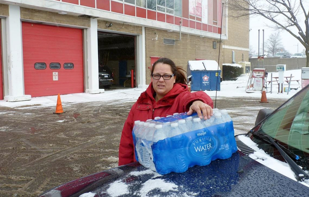 """Rabecka Cordell picks up a case of bottled water outside the fire station in Flint, Michigan. """"We both have lead poisoning,"""" said Cordell, who learned that two weeks ago from her doctor. She says she has leukemia and her son has learning and speech disabilities. She will not even bathe in Flint water and won't wash her son in it."""