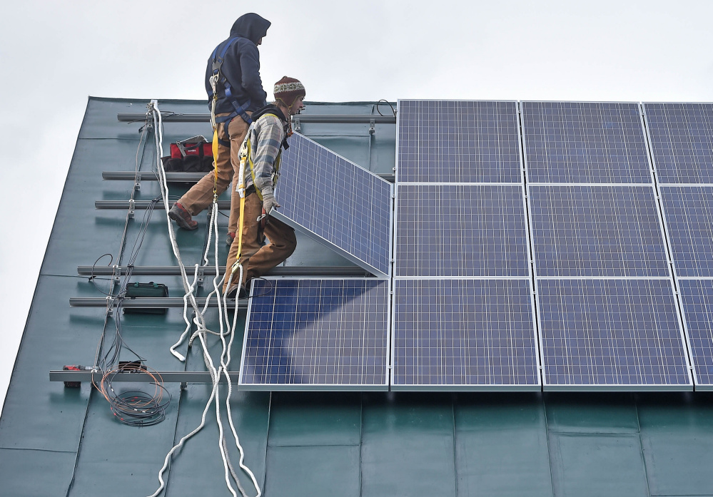 Ben Holt, foreground, and Jake Hunt, back, install a solar panel Tuesday on the Vassalboro Friends Meeting building in Vassalboro.