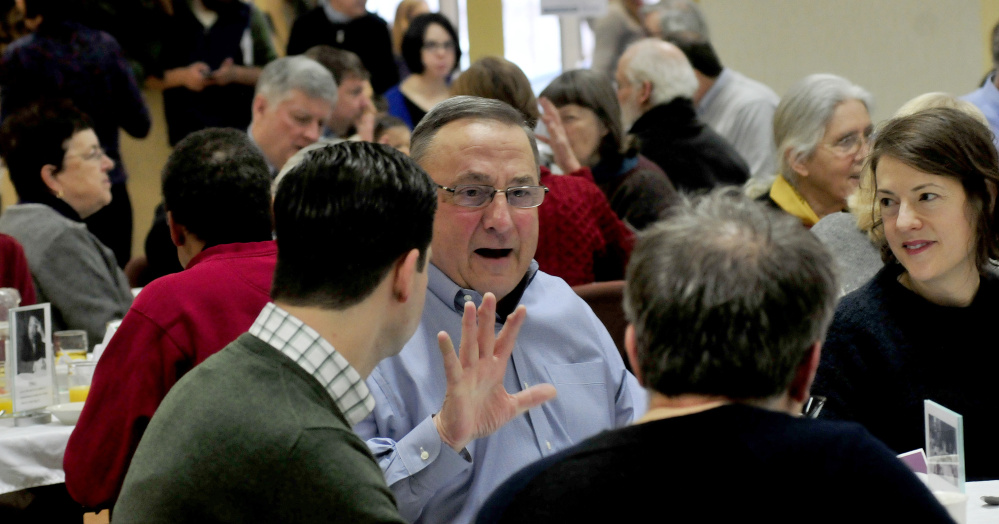 Gov. Paul LePage gestures while speaking with Waterville Mayor Nick Isgro and Sharon Corwin during the 30th annual Martin Luther King Jr. breakfast event at the Muskie Center in Waterville on Monday.