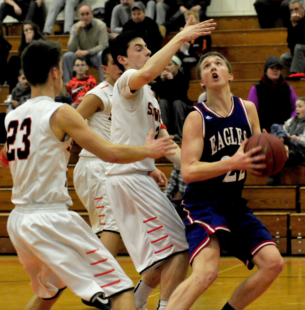 Messalonskee's Griffin Tuttle looks to shoot as Skowhegan's Brendan Curran (23) and Cameron Barnes apply pressure during a Kennebec Valley Athletic Conference Class A game Monday afternoon.
