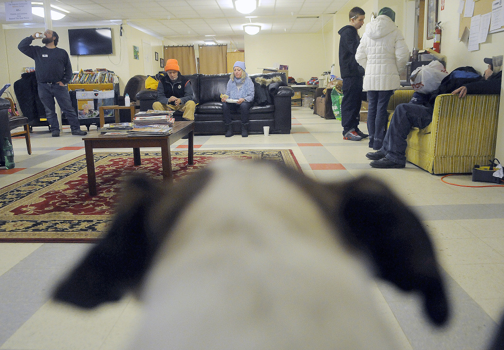 Guests, a dog and volunteers eat and warm up Tuesday at the Augusta Community Warming Center on a day when the temperature was 14 degrees.