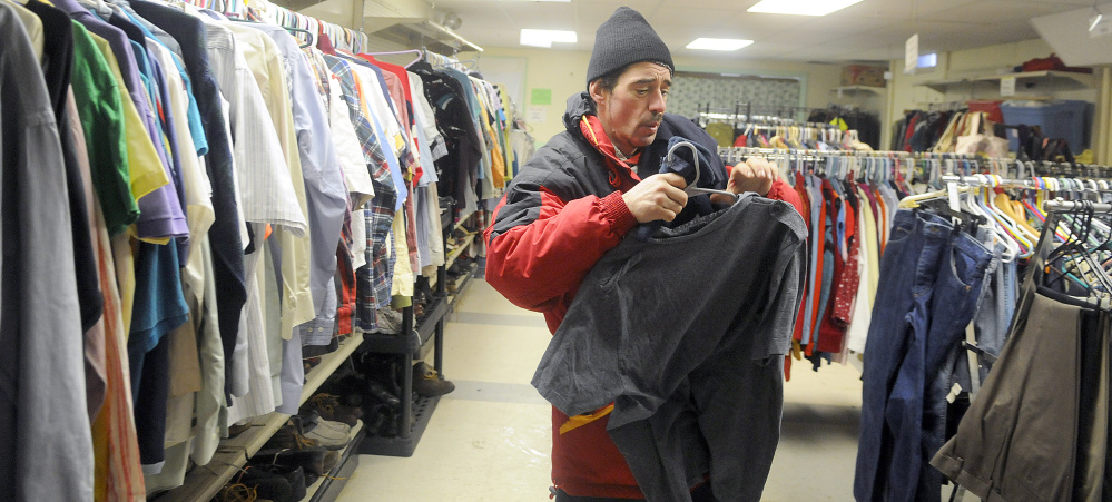 James Larrabee collects clothes in Addie's Attic Tuesday next to the Augusta Community Warming Center in Augusta.