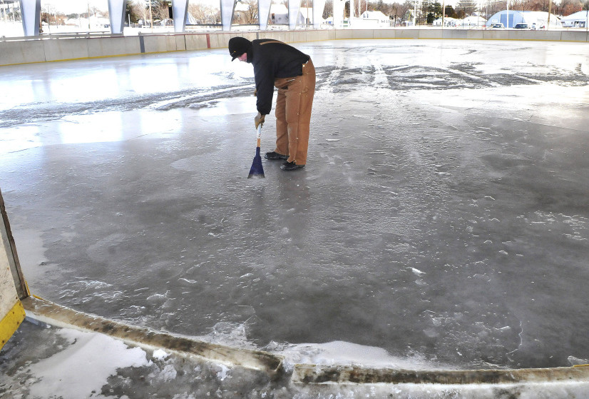 Stephen McDaniel of the Skowhegan Parks and Recreation Department on Wednesday uses a chisel too check depth of ice at public ice skating rink, which will open Thursday at the Skowhegan Fairgrounds.