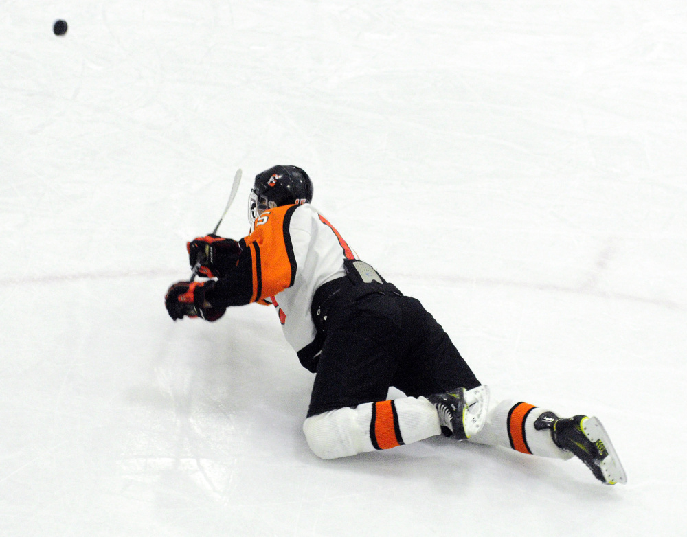 Logan Peacock falls down but still scores his fourth goal of the game that put the Tigers up 5-0 over Massabesic/Bonny Eagle/Old Orchard on Wednesday at Camden National Bank Ice Vault in Hallowell.