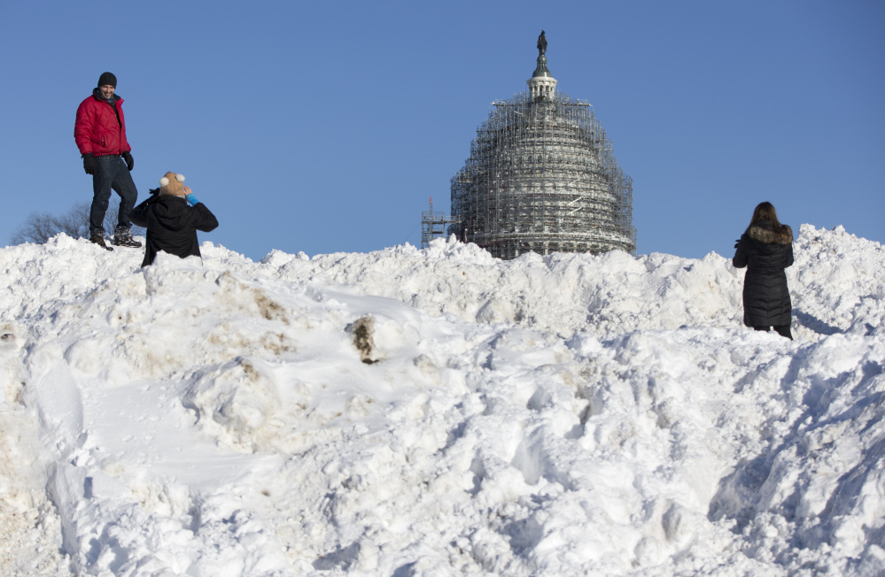 People take photographs atop a huge pile of snow in front of the U.S. Capitol in Washington on Sunday. Washington is digging out after a mammoth blizzard packed hurricane-force winds and brought record-setting snowfall.