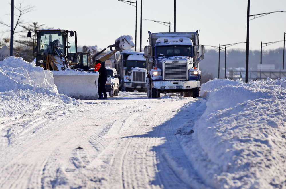 Crews work to remove the snow from a ramp for I-395 Sunday in Washington.