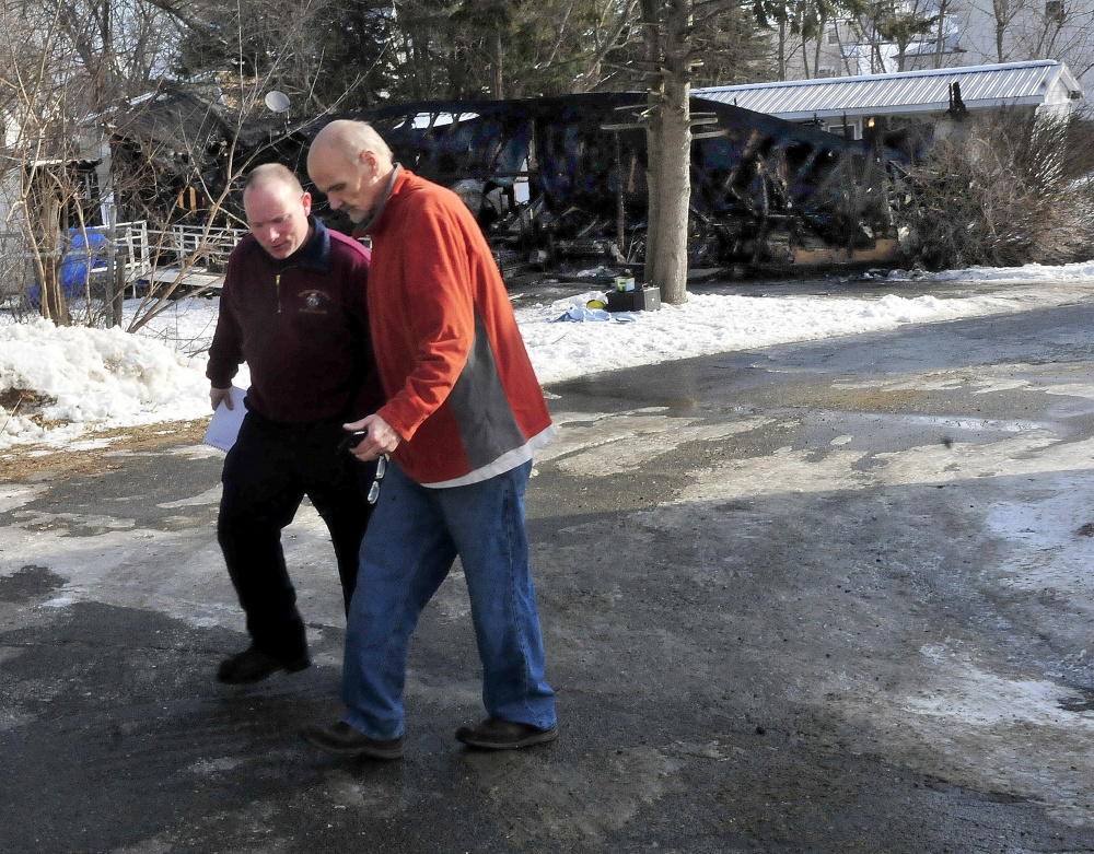 Jeremy Damren, left, of the state fire marshal's office interviews Bruce Cornforth beside the home where David Chamberlain died in a fire Monday.